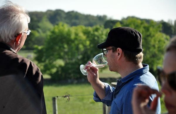 Magnus Ericsson provar vin i vingården medans CM Hedin berättar om arbetet